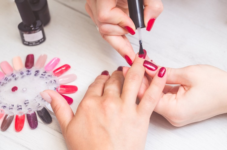 The manicurist paints the nails of women.
