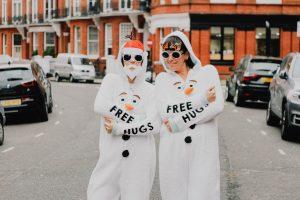 Two women wearing onesies outside