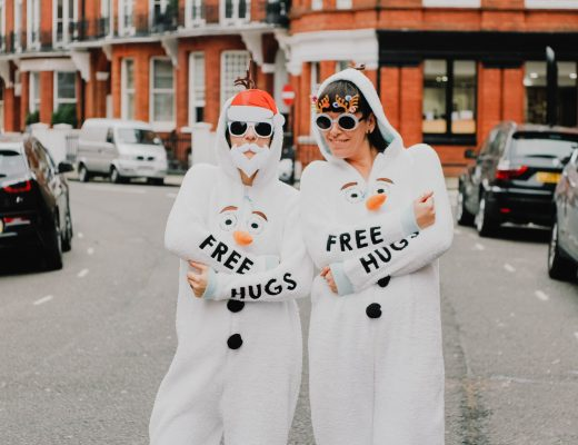 Two women wearing onesies outside