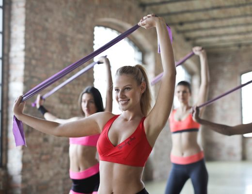 Three women wearing sports bra's in the gym.